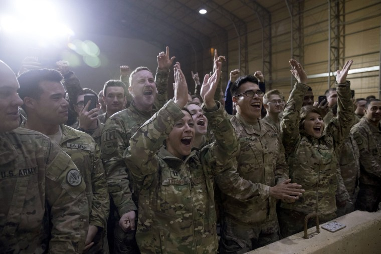 Image: U.S. troops cheers as President Donald Trump speaks at a hanger rally at Al Asad Air Base.