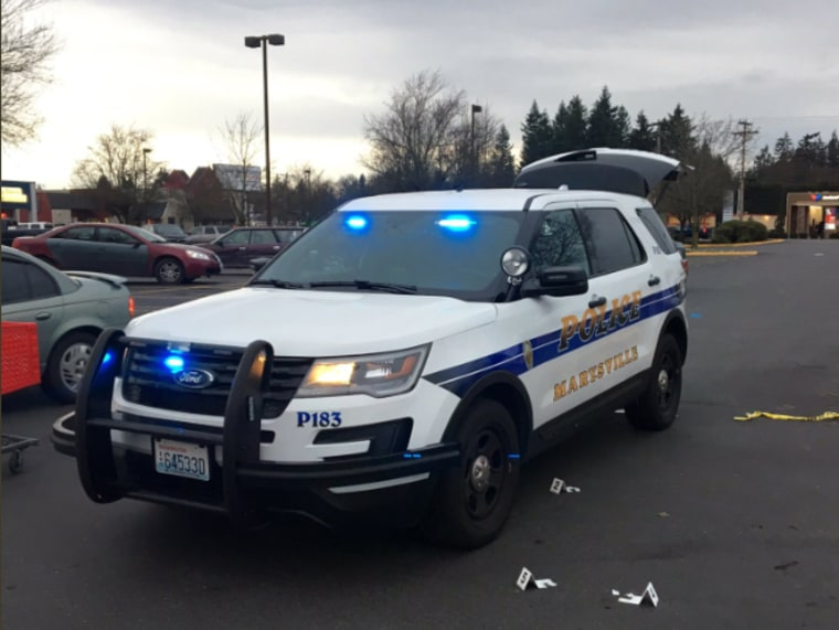 A Marysville Police Department car in the parking lot outside the store where authorities say two men attempting to steal tools were surrounded by bystanders with guns.