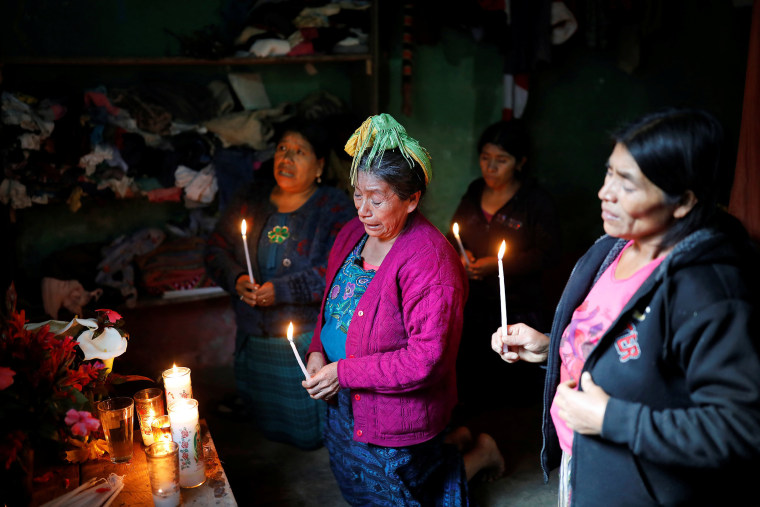 Felipe Gomez Alonzo's grandmother Catarina Perez , center, cries as she prays at an altar in her grandson's memory at the family's home in the village of Yalambojoch, Guatemala