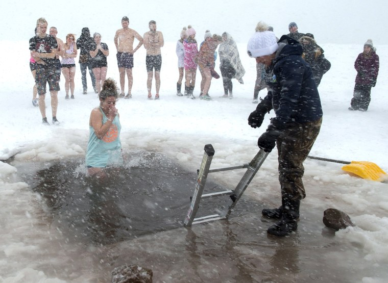 Image: Swimmers brave stormy conditions during the New Year's Polar Bear Dip on Prince Edward Island in Canada.