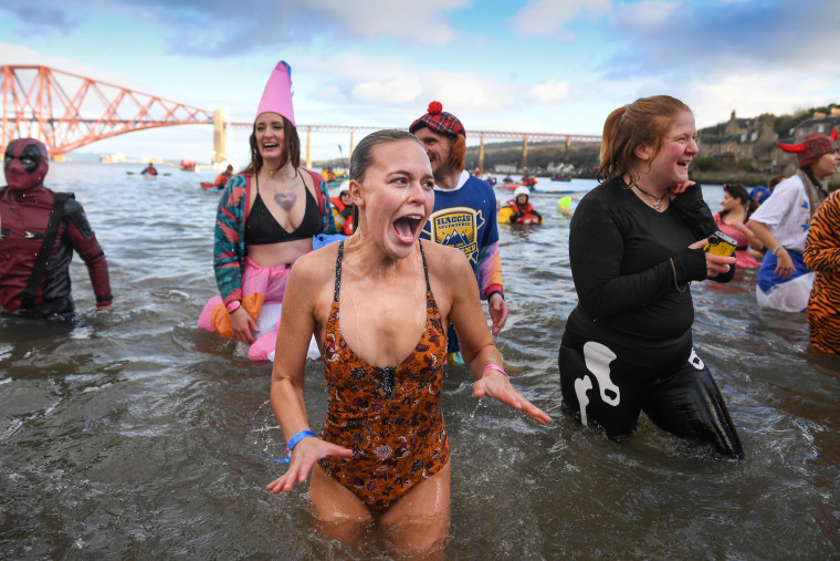 Image: Swimmers take the plunge in the Loony Dook Swim in the River Forth near Edinburgh, Scotland.