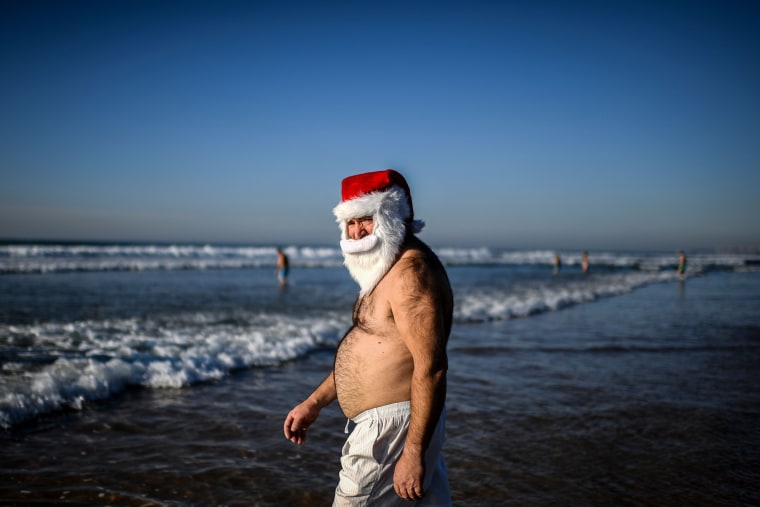 "Image: ""Santa Claus\"" treads the shore as others take the traditional dip to welcome the new year at Carcavelos Beach in Lisbon, Portugal."