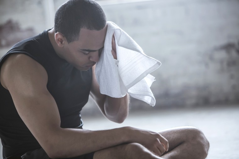 Image: Athlete wiping sweat with towel
