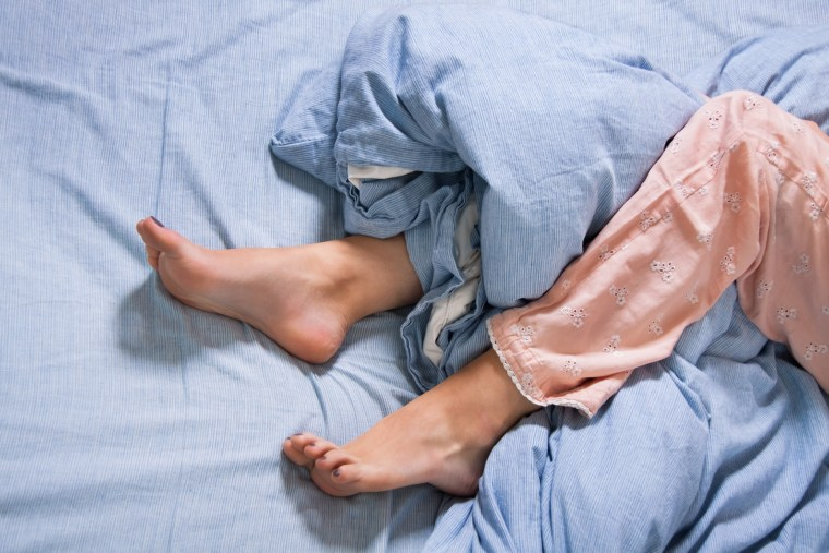 Image: Bare Feet of a Young Woman on Blue Bed