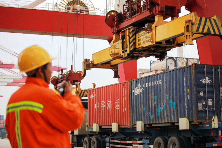 Image: An employee watches over cranes as he talks on his interphone at a port in Qingdao, east China's Shandong province
