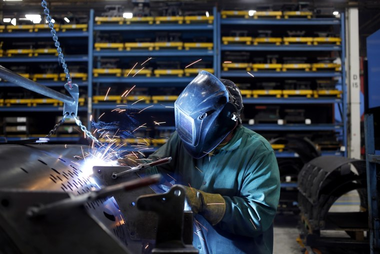 Image: A worker welds metal components onto a round baler at the New Holland Ltd. Haytools assembly plant in New Holland, Pennsylvania, on Dec. 19, 2018.