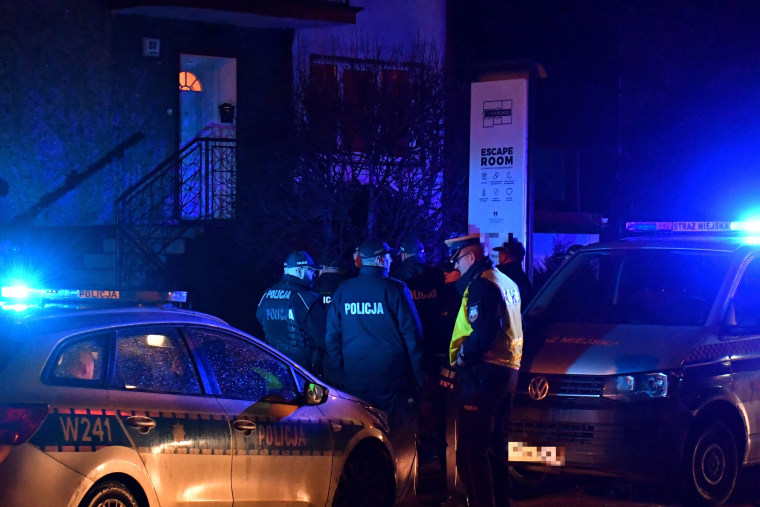 """Image: Police secure the scene of a fire in an \""""escape room\"""" that killed five teenage girls in Koszalin, Poland, on Jan. 4, 2019."""