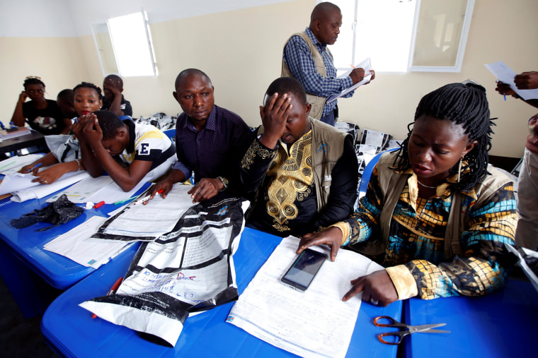 Congo's Independent National Electoral Commission officials check presidential elections polling stations voting forms at tallying centre in Kinshasa