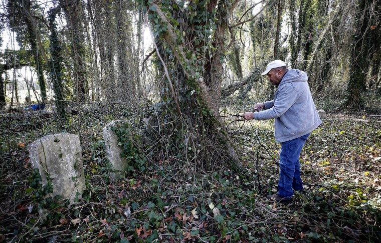 Image: Marvin Harris works to restore the Evergreen Cemetery on Dec. 5, 2019.