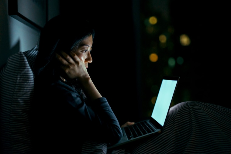 Young woman in deep thought while using laptop on bed at night