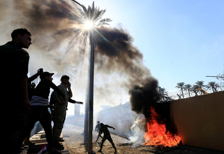 Image: Paramilitary fighters set the wall of the U.S. Embassy on fire in protest of recent airstrikes in Baghdad, Iraq, on Dec. 31, 2019.