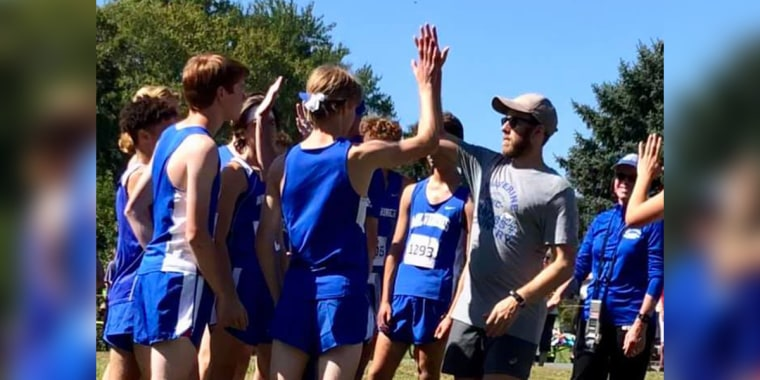 Josh Folsom, 17, high fives his high school cross country coach during the final race of his senior year season at West Potomac High School, Alexandria, VA.