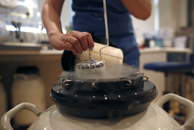 Image: An employee arranges a test tube in a container used to freeze human eggs in a laboratory