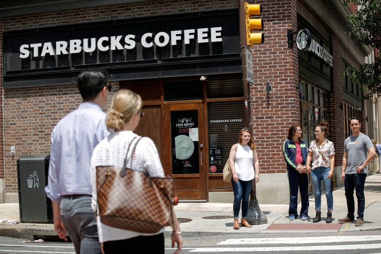 Pedestrians walk outside the Spruce St. Starbucks store, which was closed to conduct employee training on racial bias, on May 29, 2018 in Philadelphia.