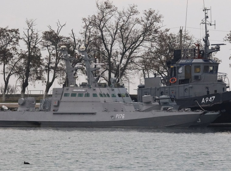 Image: Seized Ukrainian ships, small armoured artillery ships and a tug boat, are seen anchored in a port of Kerch