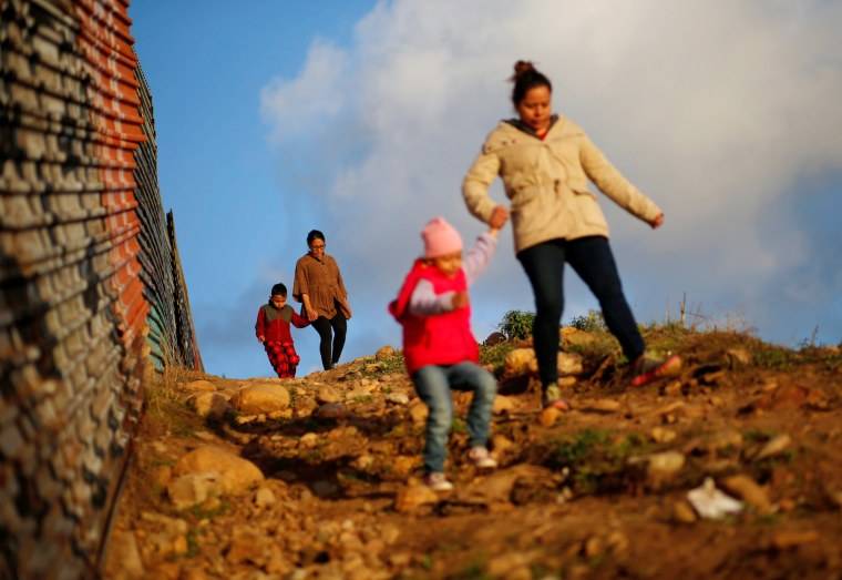 Image: Migrants from Honduras, part of a caravan of thousands from Central America trying to reach the United States, walk next to the border fence as they prepare to cross it illegally, in Tijuana,