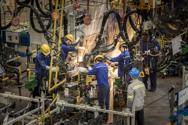Image: Sparks fly as employees work in the weld shop at the SAIC-GM-Wuling Automobile Co. Baojun Base plant in Liuzhou, China, on May 23, 2018.