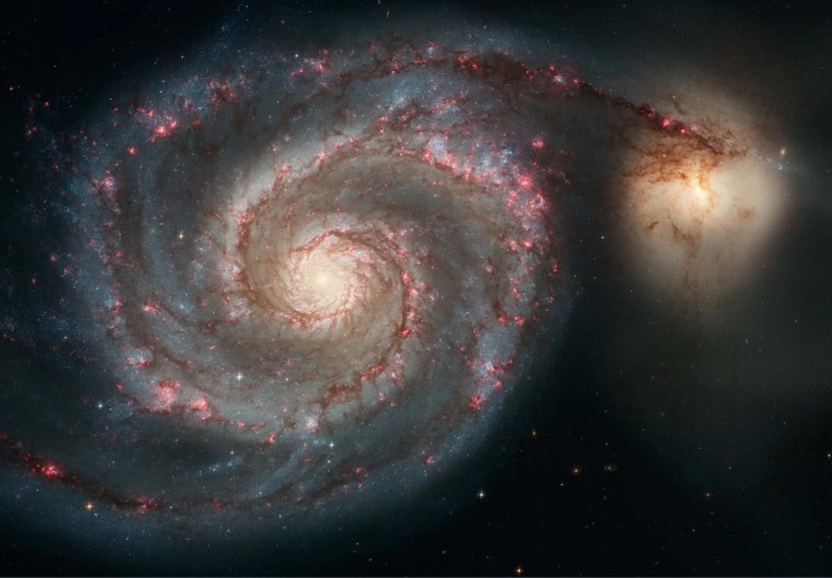 In this Hubble image, the Whirlpool Galaxy (M51a) and a companion (M51b) are merging. The two galaxies are similar in mass to the Milky Way and the Large Magellanic Cloud.