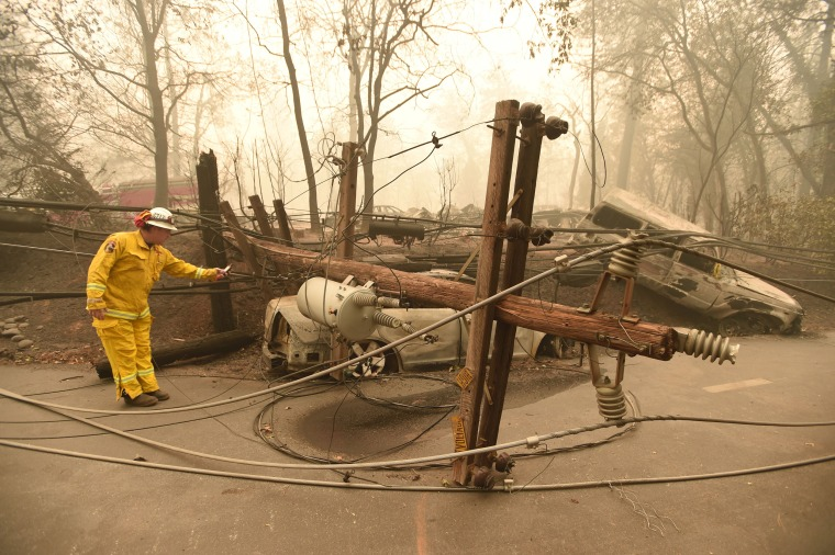 Image: CalFire firefighter Scott Wit surveys burnt out vehicles near a fallen power line after the Camp fire tore through Paradise, California, on Nov. 10, 2018.