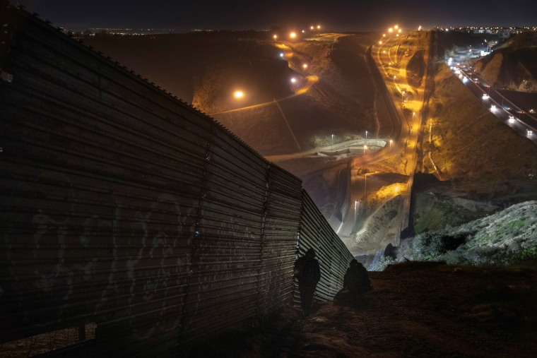 Image: Migrants looks for a place to jump over the border fence to enter the United States from Tijuana, Mexico, on Dec. 29, 2018.