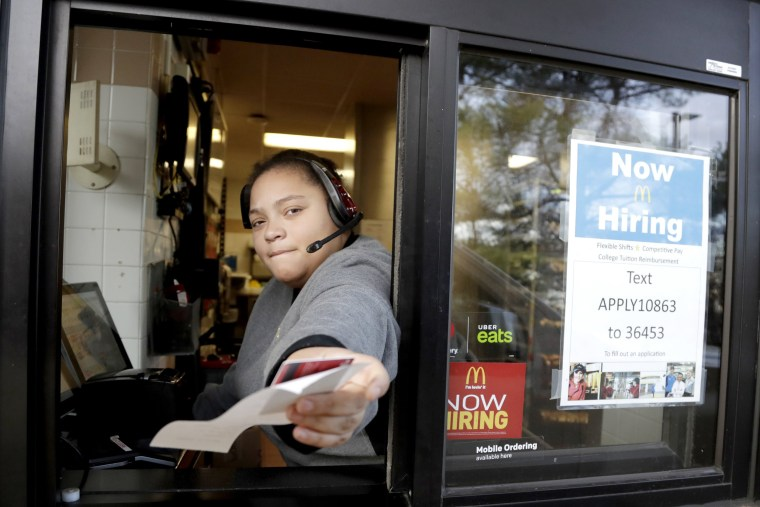 Image: A cashier returns a credit card and a receipt at a McDonald's window, where signage for job openings are displayed,
