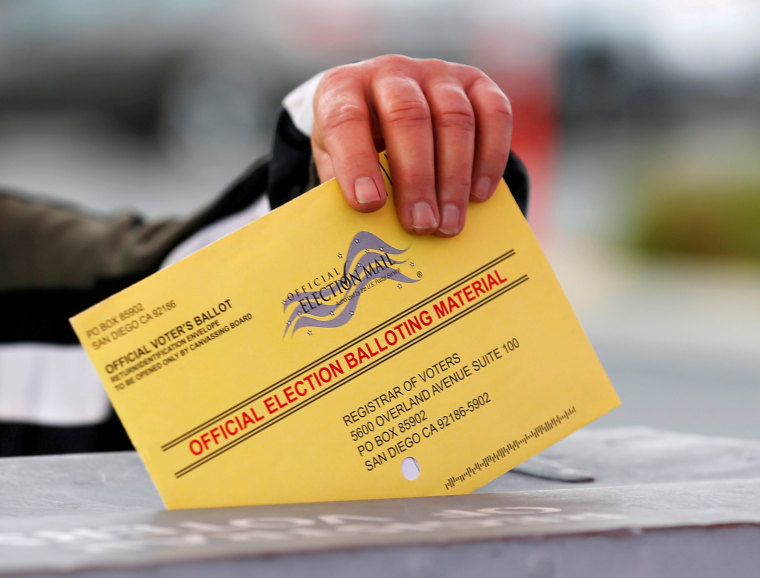 Image: A poll worker places a mail in ballot into a voting box as voters drop off their ballot in the U.S. presidential primary election in San Diego, California