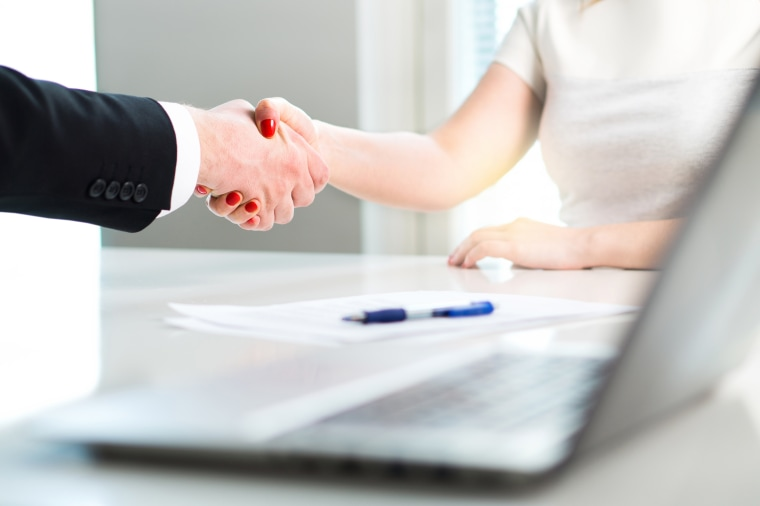 Image: Business man and woman shaking hands after successful job interview or meeting.