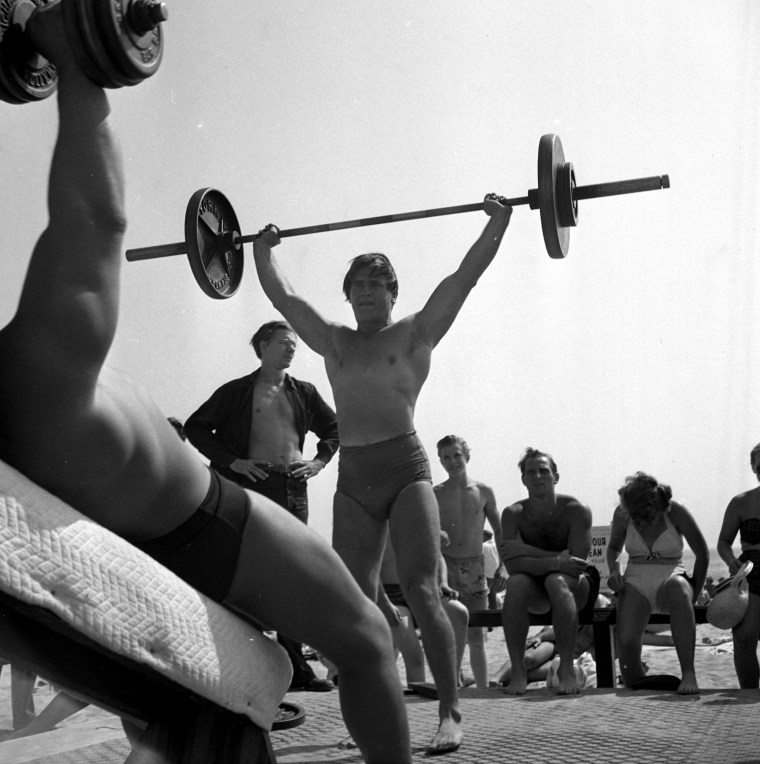 A muscle builder lifts weights at Muscle Beach
