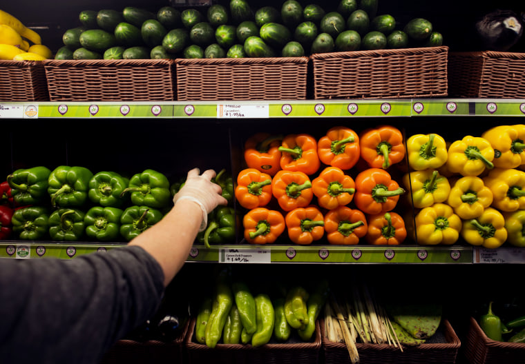 Image: An employee stocks the shelves with fresh peppers in the produce section of a Whole Foods Market store in Dublin, Ohio, on Nov. 7, 2014.