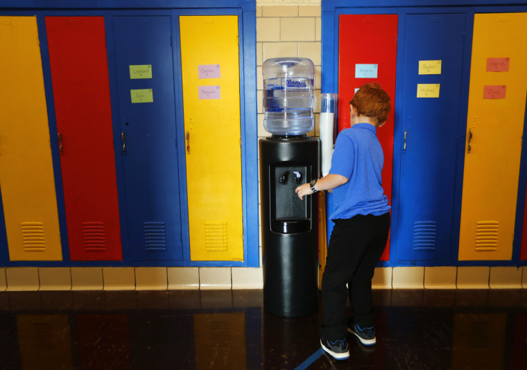 A student gets water from a cooler in the hallway at Gardner Elementary School in Detroit