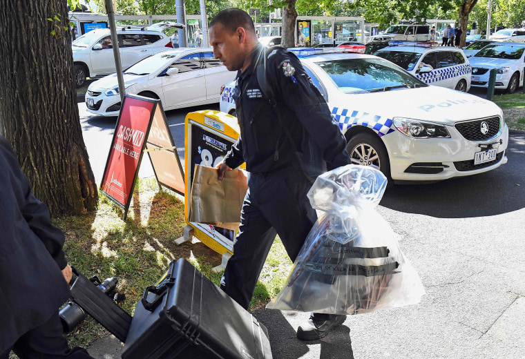 Image: A Victoria Police forensic officer carries items to be loaded into a trailer outside the Italian consulate in Melbourne