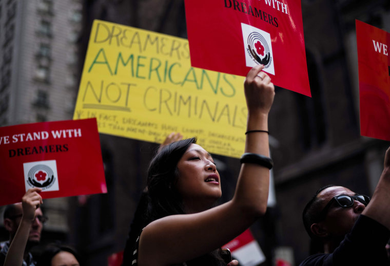 Image: Protesters hold up signs supporting DACA