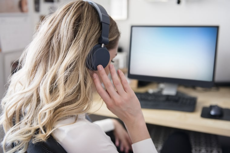 A woman with headphones at a desk