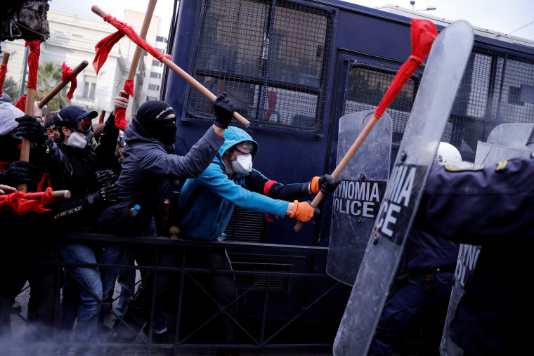 Image: Protesters clash with riot police during a demonstration of Greek school teachers outside the parliament building against government plans to change hiring procedures in the public sector in Athens