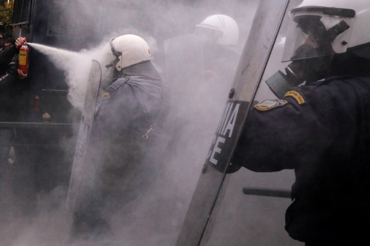 Image: A protester uses a fire extinguisher against riot police during clashes outside the parliament building as Greek school teachers demonstrate against government plans to change hiring procedures in the public sector in Athens