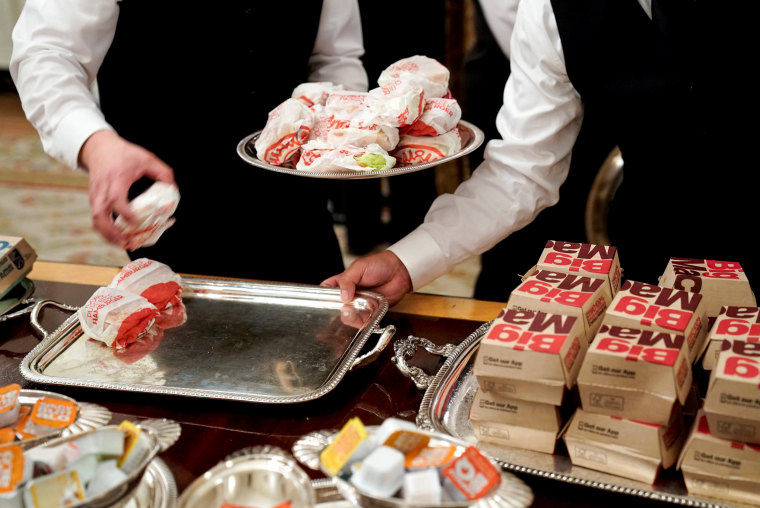 Image: Servers place hamburgers on trays as the Clemson Tigers are welcomed to the State Dining Room of the White House on Jan. 14, 2019.