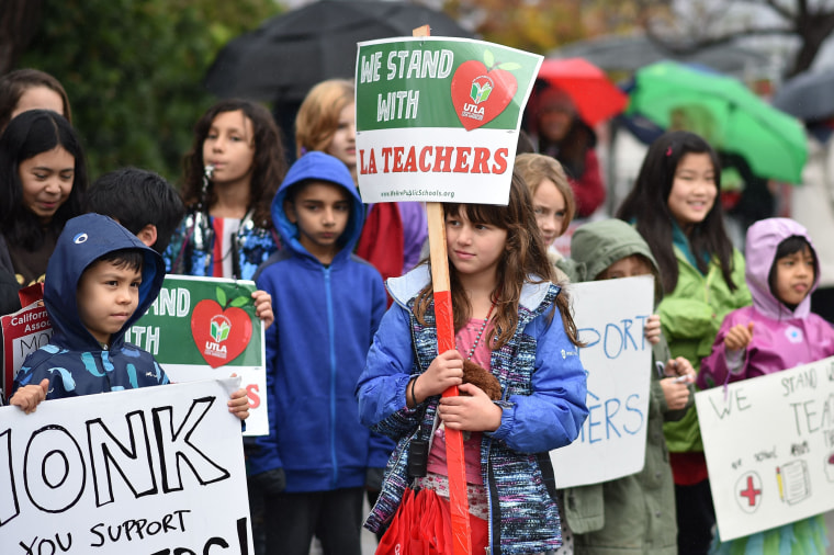 Students stand for a photo after walking the picket line with their teachers and parents