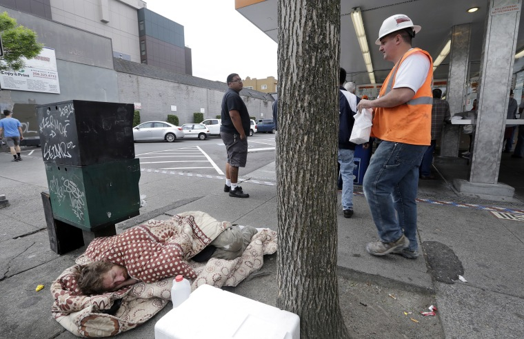 Image: A man sleeps on the sidewalk as people behind line-up to buy lunch at a Dick's Drive-In restaurant in Seattle