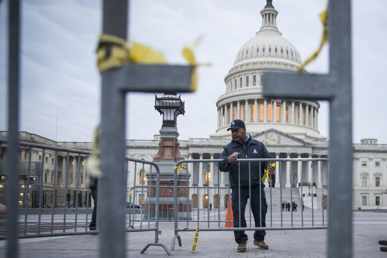 Image: A maintenance worker arranges fencing on the West Front of the U.S. Capitol before members of the 116th Congress are sworn in, on the 13th day of a government shutdown in Washington.