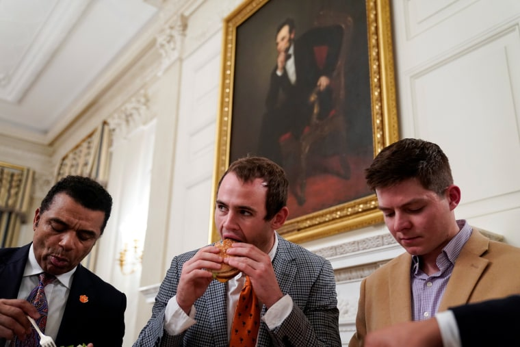 Image: Clemson wide receiver Hunter Renfrow (C) eats a fast food hamburger as the 2018 College Football Playoff National Champion Clemson Tigers are welcomed in the State Dining Room of the White House due to the partial government shutdown in Washington