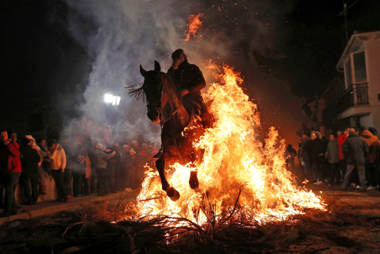 "Image: A rider goes through flames during the annual ""Luminarias"" celebration northwest of Madrid"