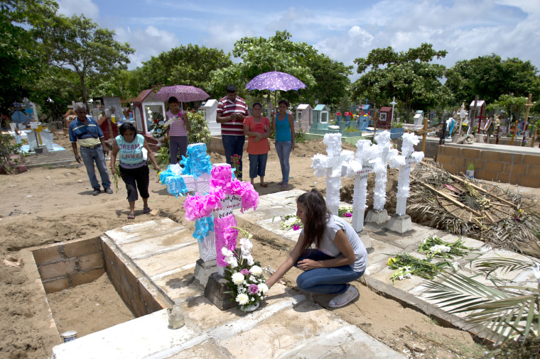 Aunts, uncles and grandparents place flowers and home-made concrete crosses atop the graves of the Martinez children, their mother and father at a cemetery in Coatzacoalcos, Veracruz State, Mexico on July 2, 2017.
