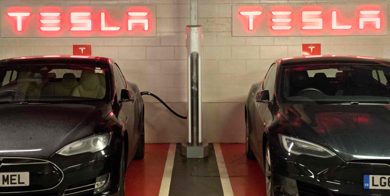 Tesla electric cars are charged at a Tesla Supercharger station, in Westfields shopping center in west London on Dec. 19, 2017.