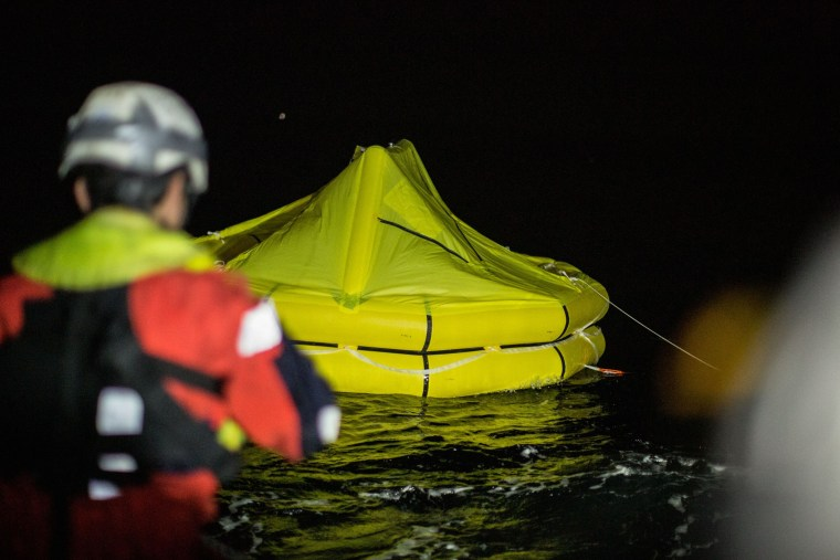 Image: Rescuers drop a life raft after a rubber dingy capsized off the coast of Libya