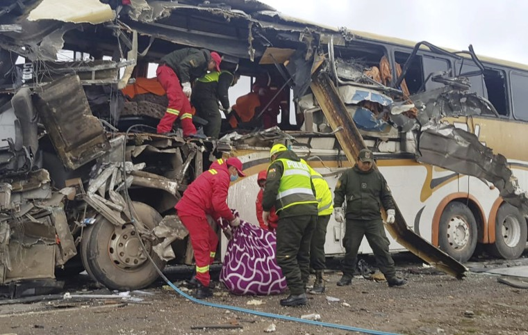 Firefighters and police help a victim of a crash of two buses on the outskirts of Challapata, Bolivia, on Jan. 19, 2019.