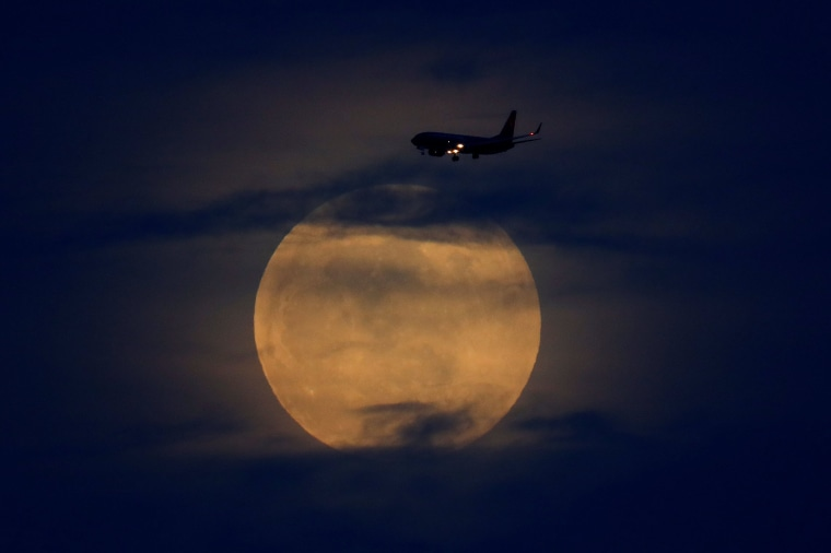 Image: A  plane passes  as the moon rises through clouds before start of total lunar eclipse in California