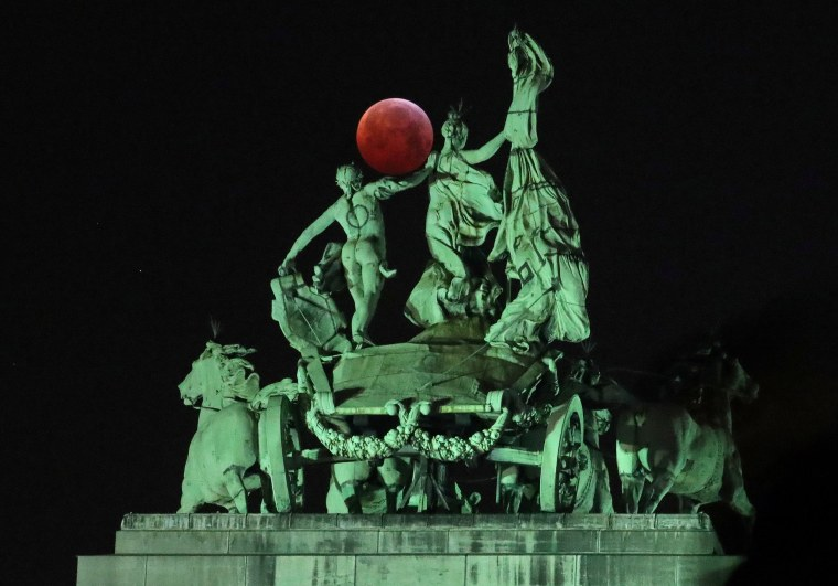"Image: The moon is seen beside a quadriga on the top of the Cinquantenaire arch during a total lunar eclipse known as the ""Super Blood Wolf Moon"", in Brussels"