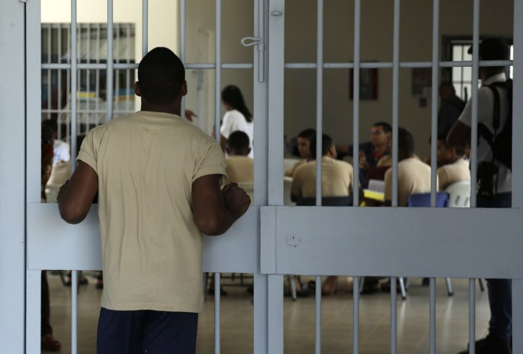 Image: A young inmate looks at another group of fellow inmates during choir practice at the Las Garzas de Pacora detention center, Panama