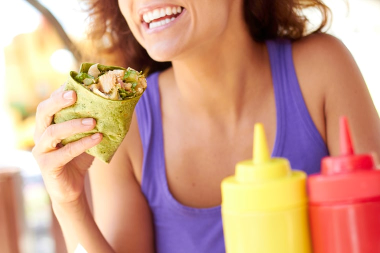 Image: Woman Holding Chicken Wrap in a green spinach tortilla