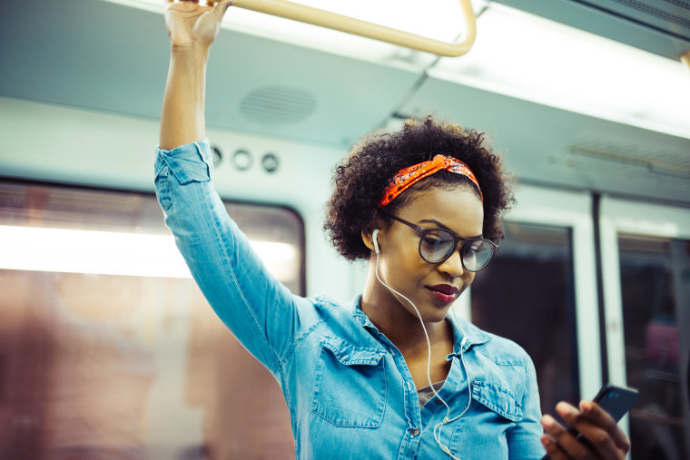 Image: Smiling young African woman listening to music on the subway